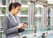 Hispanic Businesswoman Outside Office On Mobile Phone