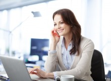 Beautiful business woman working on laptop while talking on mobile phone at office